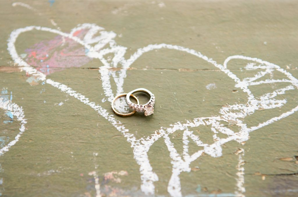 two wedding rings in a chalk heart drawing