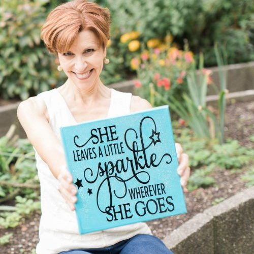 "Annemarie Juhlian, Seattle Wedding Officiant - holding a sign ""She Sparkles wherever she goes"""